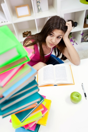 unmotivated: worried student girl looking in books Stock Photo