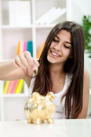 Cute teen girl putting coin in piggybank, increasing savings photo