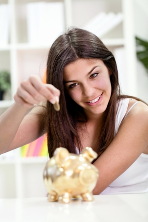 Teenager girl putting coin in golden piggybank banking, investment, photo