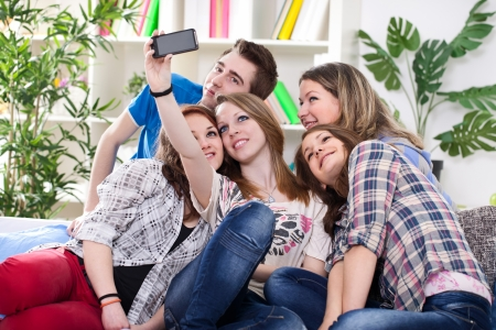 Happy teenagers taking group photo with smartphone photo