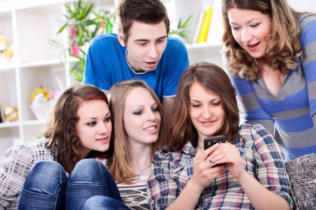 telephone together:  Surprised friends reading interesting sms looking in smart phone