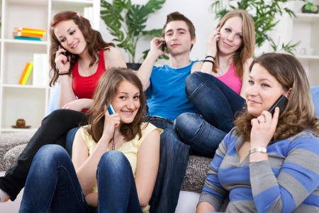 Teenager friends using mobile phones photo