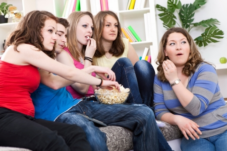 Group of friends watching TV, something very interested happened on the screen. photo