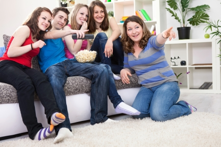 Friends looking something funny on TV and laughing, sitting in living room  photo
