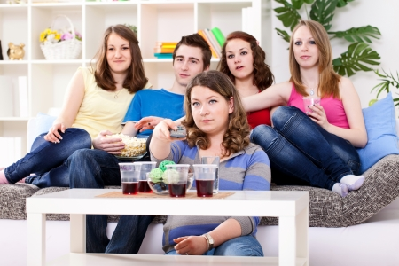 Teenagers  watching TV, girl holding remote control photo