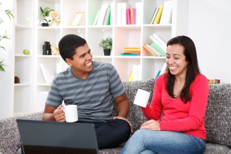young laughing couple drinking coffee in living room Stock Photo - 13888170