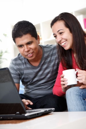 Young people sitting on couch and using laptop at home Stock Photo - 13888272