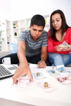 Happy young couple sorting out their home finances. Stock Photo - 13888137