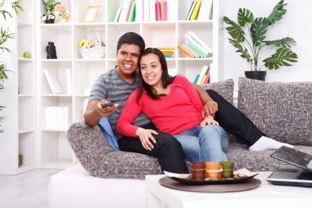 Smiling young couple watching TV on couch at home  photo