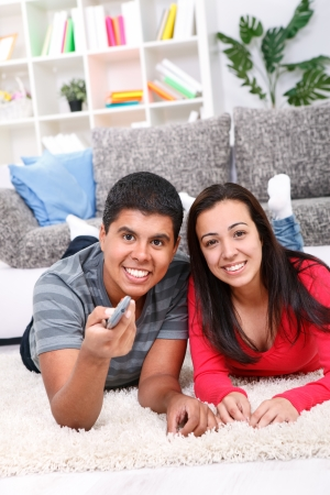 Portrait of a cute couple watching TV in their living room Stock Photo - 13888173