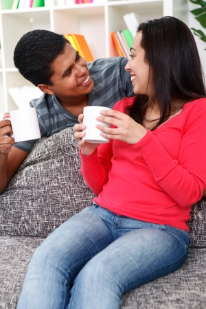 Young couple drinking coffee at home sitting on couch, smiling and looking at each other photo