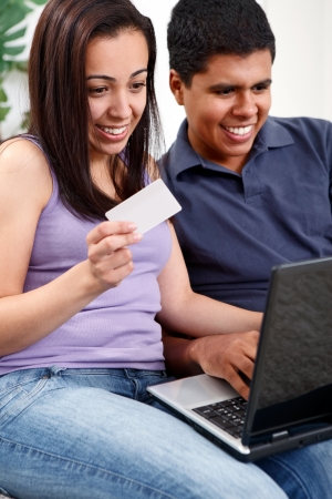 Young couple doing shopping in internet with credit card at home. Stock Photo - 13888246