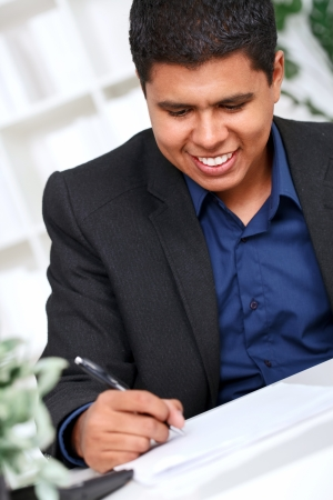 Smiling businessman taking notes at office desk , hand with pen in focus Stock Photo - 13888130