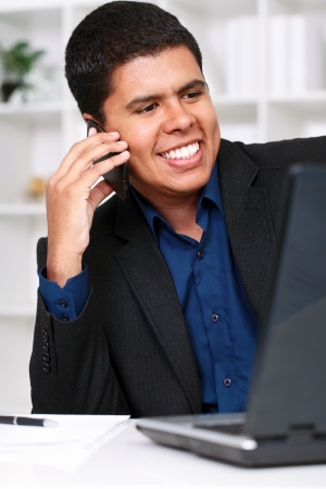 successes: Young handsome businessman talking on phone and smiling