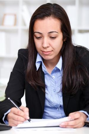 concentrate young business woman writing a contract in office Stock Photo - 13888164
