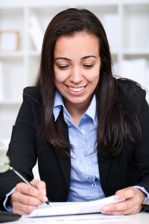 young businesswoman making note, sitting on desk in office  Stock Photo - 13888118
