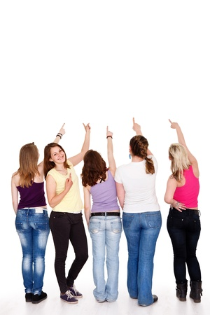 funny teenager girls pointing in copy space above them showing, photo