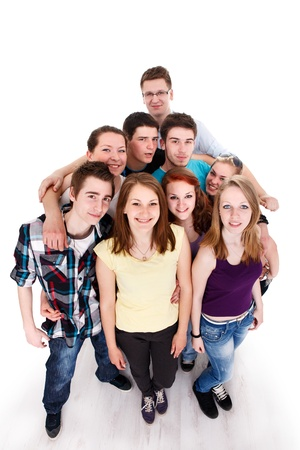 Happy smiling group of young friends standing and embracing together, top view photo