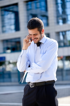 Young Caucasian businessman talking on smart phone outside modern office block photo
