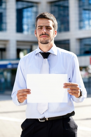 Businessman holding a blank sign front of office building photo