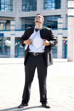 Superhero businessman ripping off his blue shirt, businessman in action photo