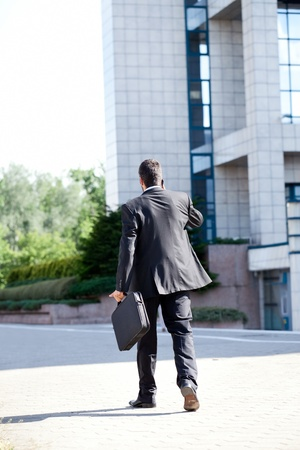 Business man leaving after a working day , end of a business day, back view photo