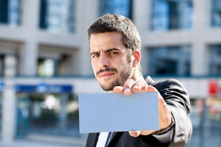 Handsome businessman holding blank business card, outdoor photo