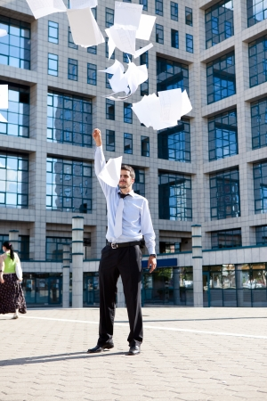 throws: young business man throws upwards paper documents