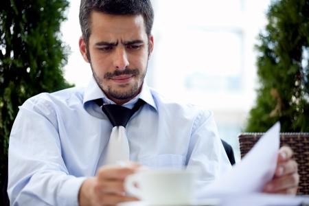 Handsome businessman reading paperwork, outdoor photo