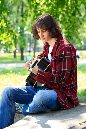 young man playing the guitar, outdoor photo