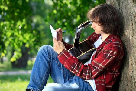 man playing guitar: Man composing song on guitar in park