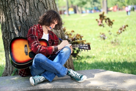 Young man composing for acoustic guitar in park photo