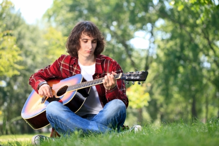 Musician in park playing his guitar photo