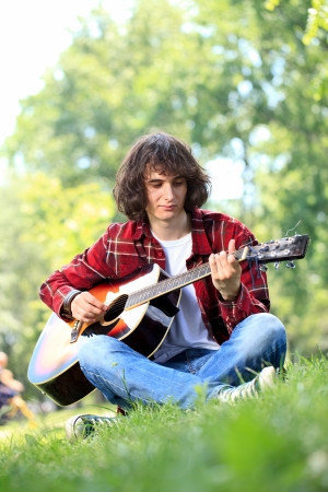 Young man sitting on grass an playing guitar photo