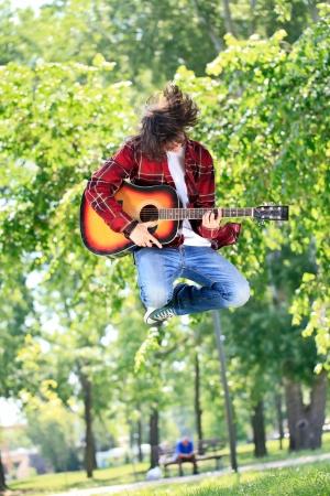 persona saltando: Salto Chico joven con la guitarra en el parque
