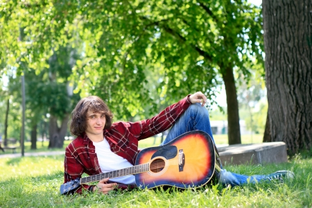 Young man in park with acoustic guitar photo
