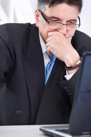 unhappy worker: Upset senior businessman worried watching in laptop