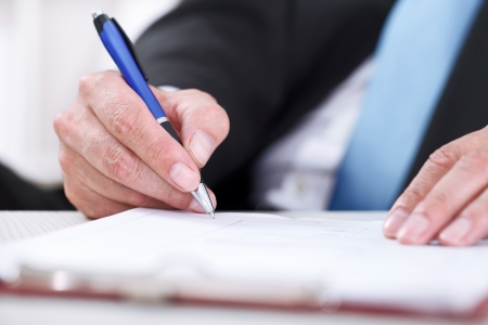 Businessman sitting at office desk signing a contract with focus on signature. Stock Photo