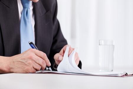 firmando: hombre de negocios la escritura a mano en papel de cerca Foto de archivo