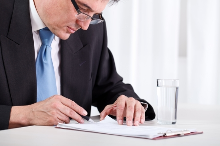 Senior businessman concentrate reading and  checking contract photo