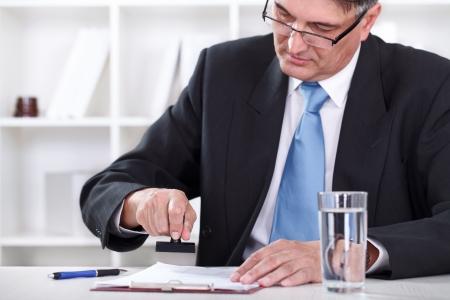 emboutissage: concentr� d'affaires senior sur estampage document, Approbation du contrat Banque d'images