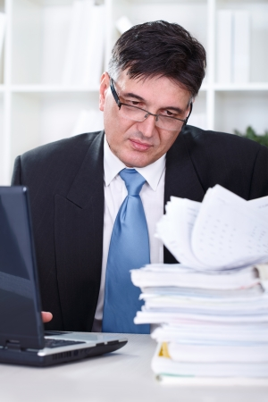 entering information: Senior businessman transferring data to the computer, working in office