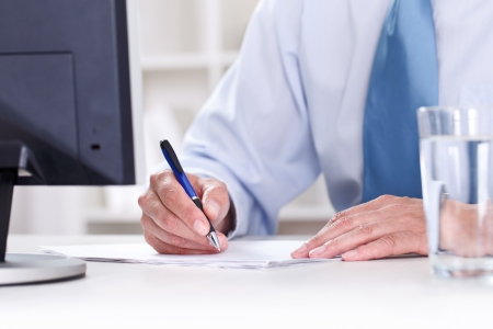 Businessman in blue shirt sitting at office desk signing a contract  photo