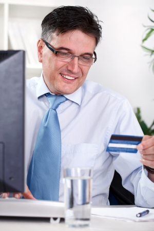 Smiling mature businessman holding credit card, online shopping  photo