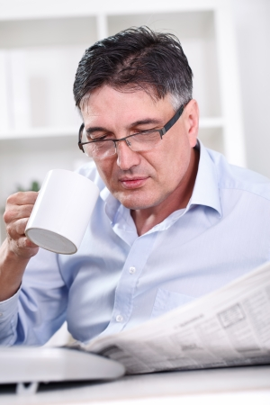 Senior businessman on coffee break in office lobby, reading papers, holding coffee cup,  photo