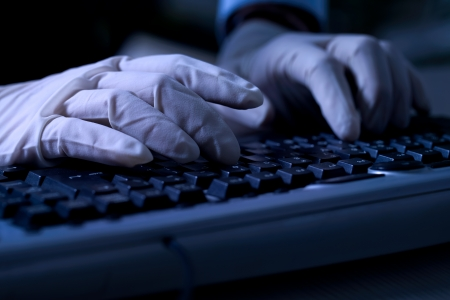 identity thieves:  Computer hacker with protective gloves steal data from computer Stock Photo