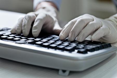 Computer hacker hand in glove working on laptop Stock Photo - 14351907