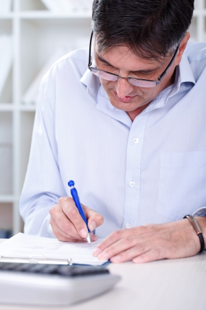 Business man sitting in office with laptop writing note photo