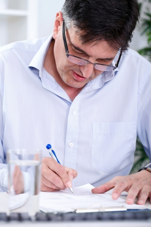Senior concentrated   business man writing in office photo