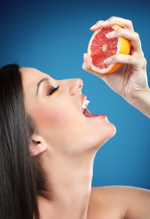 squeezing: Young beautiful woman squeezing orange into mouth, sensual refreshment